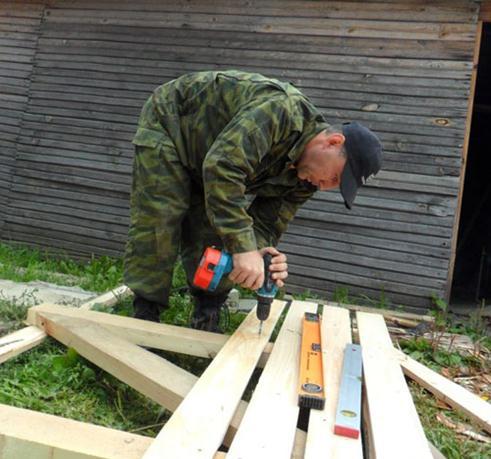 Процесс обшивки каркаса деревянных распашных ворот