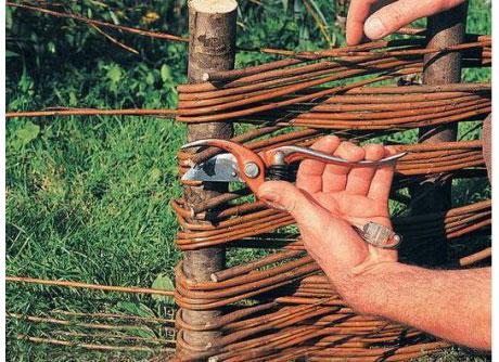 Концы веточек обогнем вокруг последнего колышкаи засунем в нутрь плетня. Высунувшиеся концы обрежем